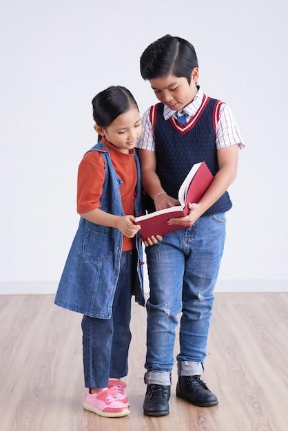 Молодой азиатский мальчик и девушка стоя совместно и смотря книгу Бесплатные Фотографии