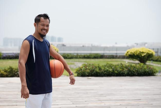 スタジアムで屋外に立って、バスケットボールを押しながら笑顔のアジア人 無料写真