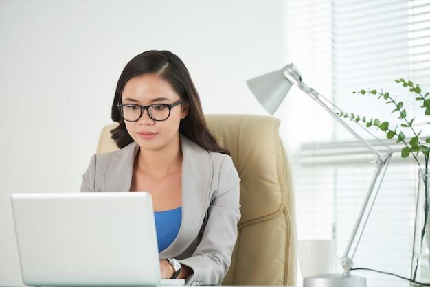 オフィスでラップトップ上のドキュメントを起草する若いビジネス女性 無料写真