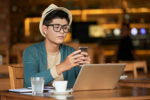 ノートパソコンとカフェに座っていると、スマートフォンを使用して若いアジア流行に敏感な男 無料写真