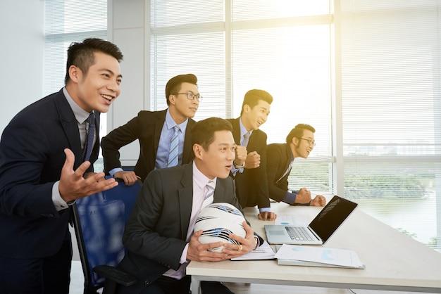 サッカーの試合を見ているアジア系のビジネスマン 無料写真