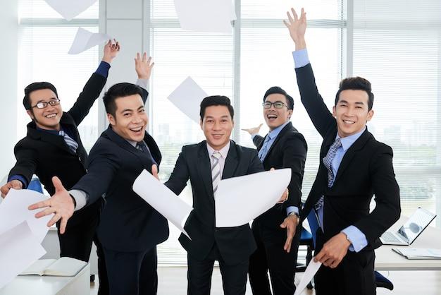 オフィスで空気中のドキュメントを投げるスーツで陽気なアジアのビジネスマンのグループ 無料写真