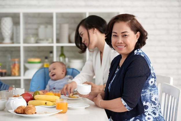 家族と一緒に朝食のテーブルでエレガントなアジアの女性 無料写真