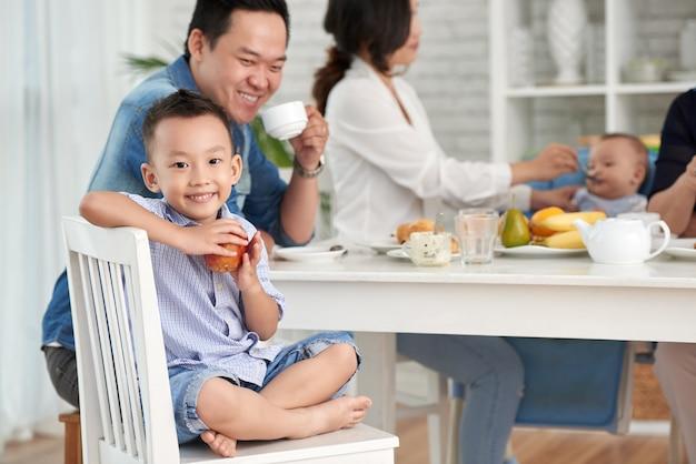 家族と一緒に朝食で幸せなアジアの少年 無料写真