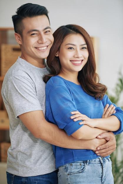 立っていると屋内で抱いて若いアジアカップルの笑みを浮かべてください。 無料写真