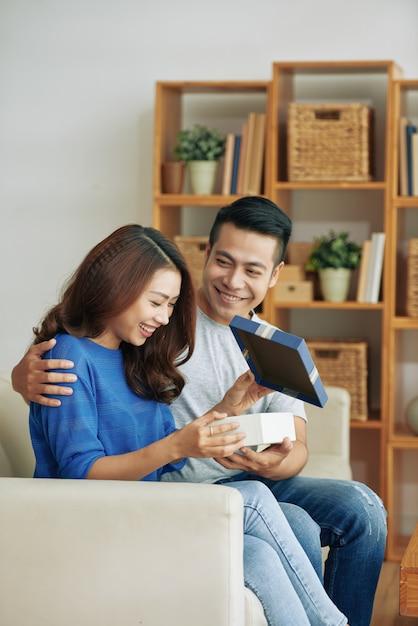 自宅でソファに座って、夫からプレゼントを得る幸せな若いアジア女性 無料写真