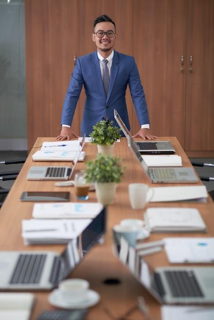 企業の会議室での長い会議テーブルの上に立っているアジア系のビジネスマン 無料写真