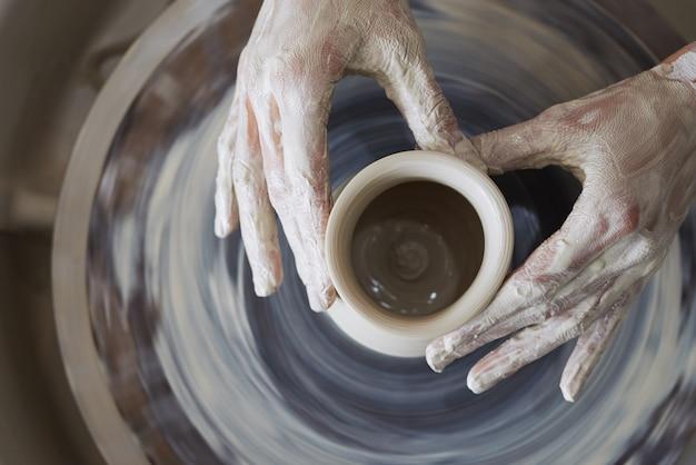 スピニングホイールに粘土の容器を彫刻する女性の陶工の手 無料写真