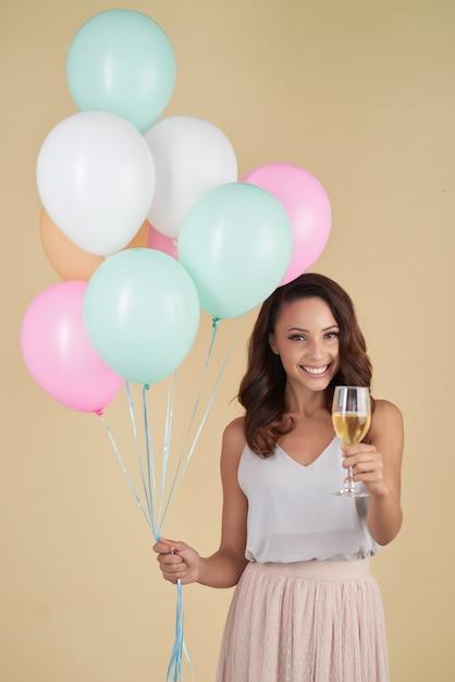 白人女性がヘリウム風船とシャンパンの束とスタジオでポーズ 無料写真