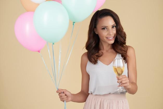 Улыбающиеся женщина кавказских позирует в студии с воздушными шарами и бокал вина Бесплатные Фотографии
