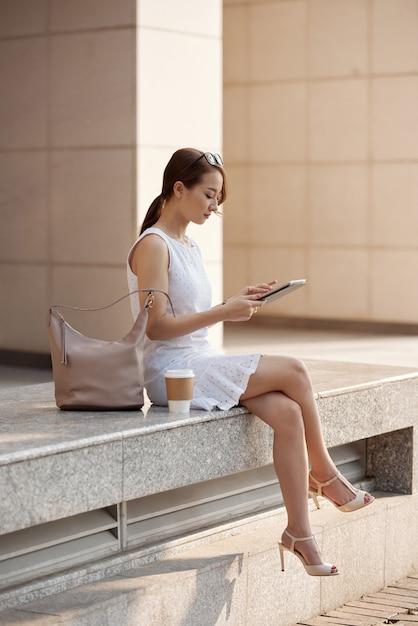 都市通りに座っていると、タブレットを使用して美しい若いアジア女性 無料写真