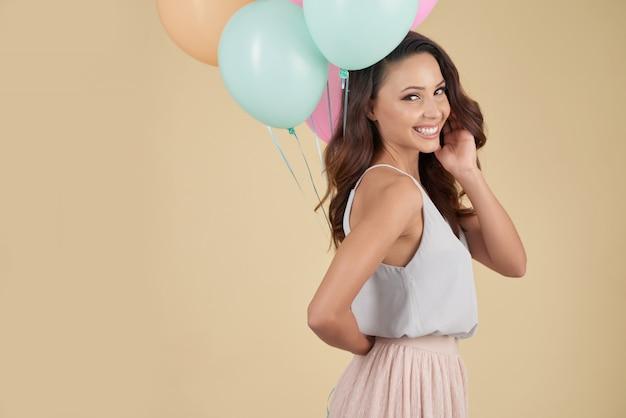 風船とスタジオでポーズをとって彼女の肩越しに見ている白人女性の笑みを浮かべてください。 無料写真