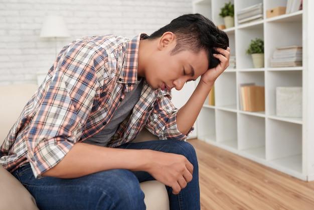 若いアジア人の頭痛に苦しんで水平サイドビューショット 無料写真