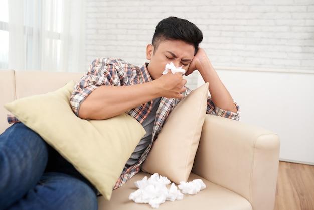 医療休暇を自宅に持っている鼻水に苦しんでいる若いアジア人 無料写真