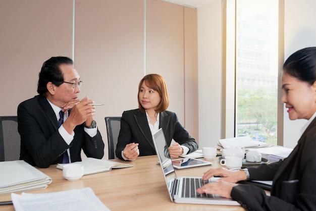会議テーブルの周りに座って話しているアジアのビジネス人々のグループ 無料写真