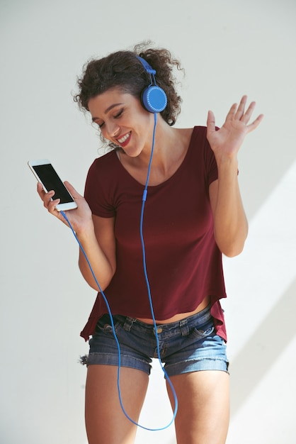 ヘッドフォンで彼女のお気に入りの曲に合わせて踊る若い女性 無料写真