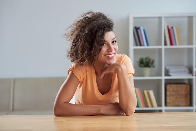 Кудрявая молодая кавказская брюнетка сидит за столом дома и улыбается на камеру Бесплатные Фотографии