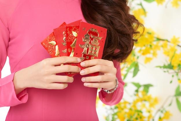 Обрезанная неузнаваемая женщина, держащая китайские новогодние подарочные карты Бесплатные Фотографии