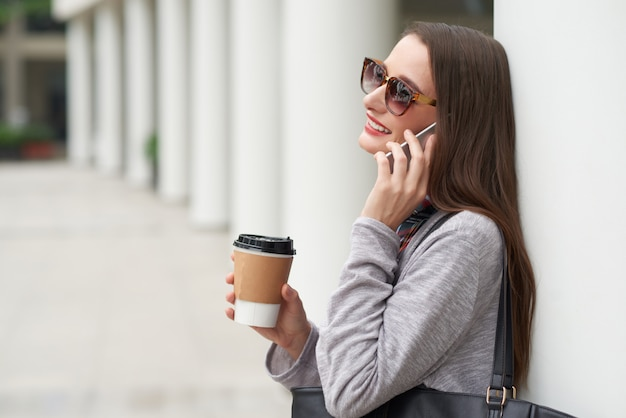建物の壁にもたれて電話をかけるサングラスの若い女性の側面図 無料写真