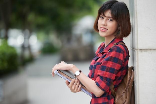 Симпатичная студентка с рюкзаком и учебниками опирается на стену здания колледжа Бесплатные Фотографии