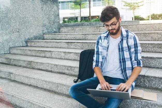 Программист работает на компьютере на мраморной лестнице на улице Бесплатные Фотографии