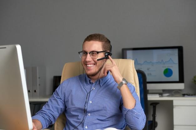 Средний снимок счастливого менеджера, работающего в колл-центре Бесплатные Фотографии