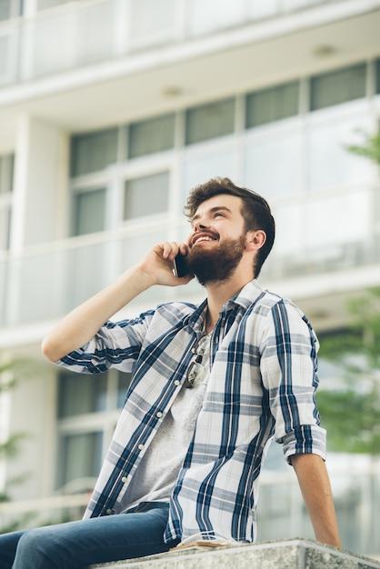 建物の外の電話で話しているひげを生やしたヒップスターの低角度のビュー 無料写真