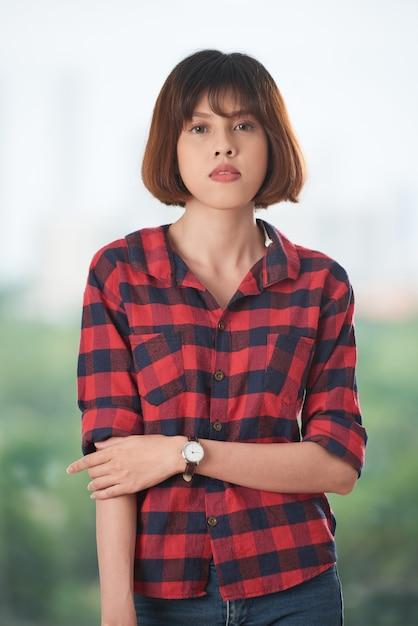 Довольно азиатская девушка, глядя на камеру в клетчатой рубашке Бесплатные Фотографии