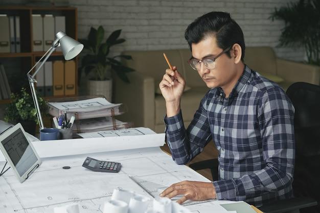 Азиатский человек, рисование план в своем уютном офисе Бесплатные Фотографии