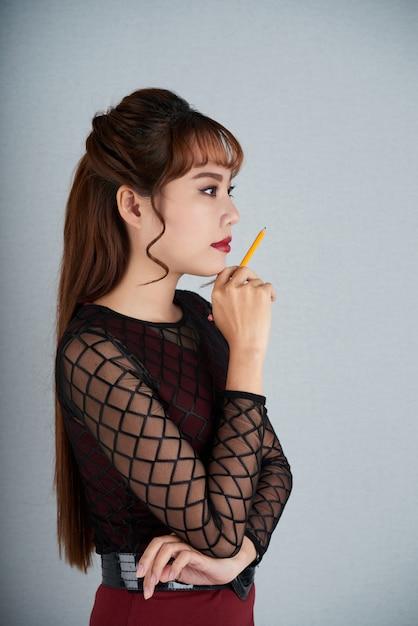 Вид сбоку девушки, размышляющей над бизнес-задачей с ручкой в руке Бесплатные Фотографии