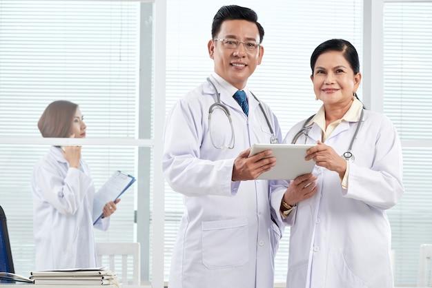 Средний снимок двух врачей, стоящих в медицинском кабинете, обсуждающих клинический случай Бесплатные Фотографии