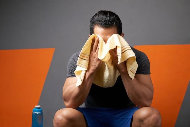 ジムの更衣室に座っているタオルで汗を拭く認識できない男性アスリートのミディアムショット 無料写真