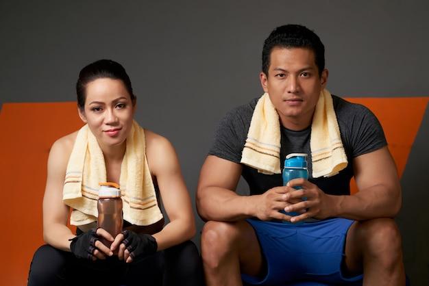 Спортивная пара смотрит на камеру, сидящую на диване после тренировки Бесплатные Фотографии