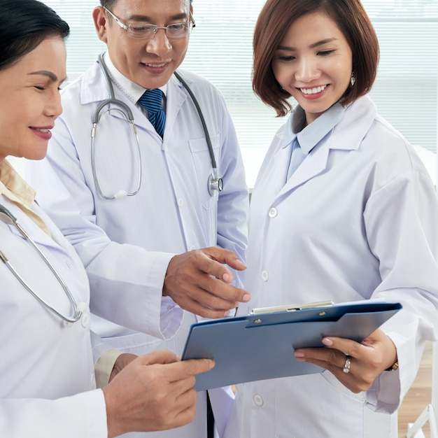 Средний снимок трех врачей, консультирующих по медицинскому делу Бесплатные Фотографии