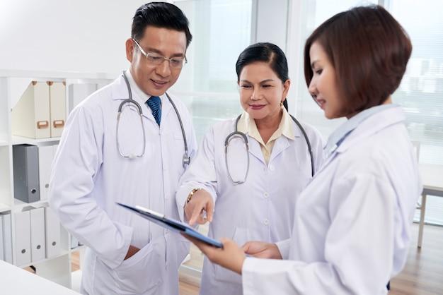 Средний снимок трех врачей, анализирующих список симптомов Бесплатные Фотографии