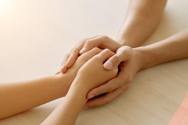 Руки анонимного поддерживающего друга, держащего руки женщины Бесплатные Фотографии