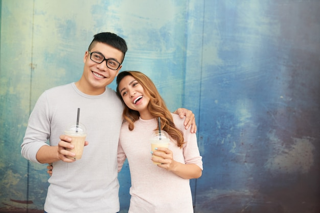 Влюбленная пара весело улыбаясь молочные коктейли Бесплатные Фотографии