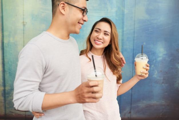 プロムナードの散歩にミルクセーキを持っているカップルのデートの側面図 無料写真