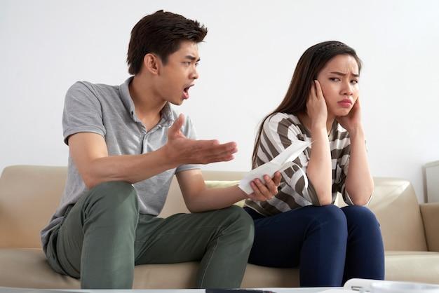 Средний снимок азиатского человека, кричащего на свою жену, держащую листок бумаги Бесплатные Фотографии