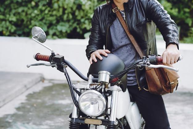 バイクに座っているヘルメットと革のジャケットで認識できない男の中間セクション 無料写真