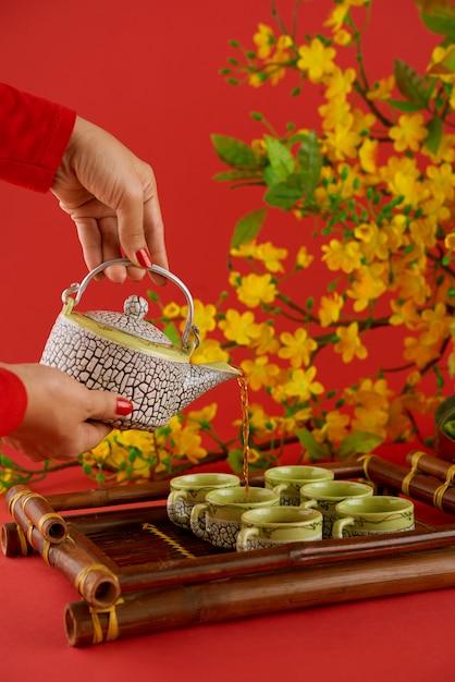 赤い背景に対して緑茶を注ぐ女性の手の側面図 無料写真