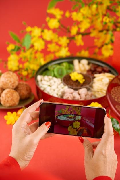 彼女のスマートフォンのカメラで伝統的な食べ物を撮影するトリミングされた女性の手 無料写真