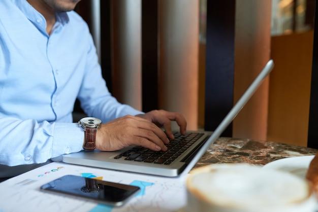 Обрезанный человек занят печатать на клавиатуре ноутбука за завтраком Бесплатные Фотографии