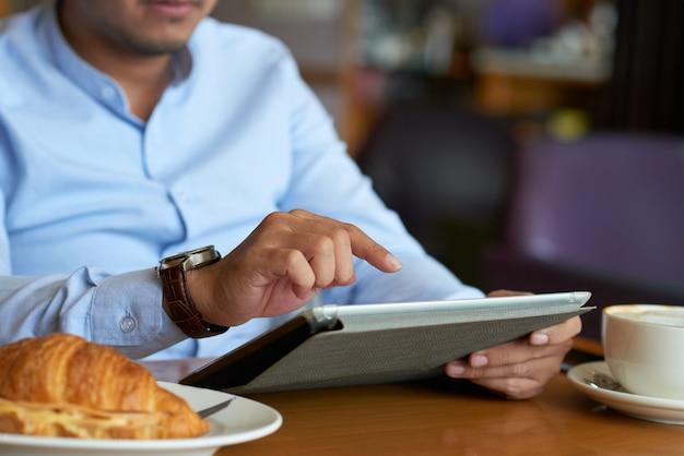 Подрезанный руководитель бизнеса используя беспроводное устройство в кафе Бесплатные Фотографии