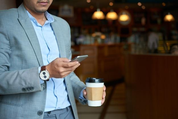 Подрезанный бизнесмен проверяя телефонную почту держа чашку на вынос кофе утром Бесплатные Фотографии