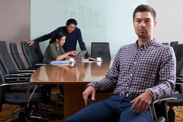 カメラ目線のオフィスの椅子に座っている青年実業家 無料写真