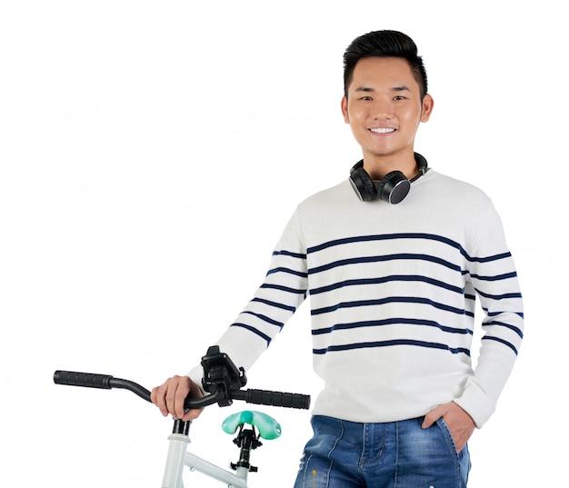 Средний снимок молодого азиатского хипстера, стоящего рядом с его велосипедом Бесплатные Фотографии