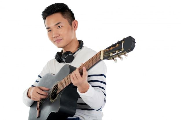Средний снимок азиатского музыканта, сочиняющего мелодию на гитаре Бесплатные Фотографии