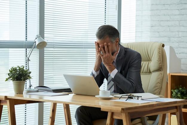 失敗に失望した彼の顔に彼の手で机に座っているビジネスマンのミディアムショット 無料写真