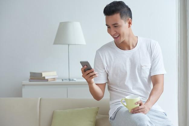 Средний снимок молодой кишки заняты текстовыми сообщениями в его социальных сетях на смартфоне утром Бесплатные Фотографии